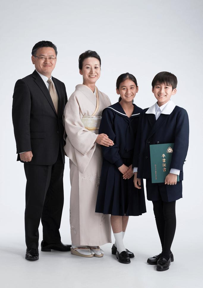 卒業証書を持って卒業記念撮影をしている4人家族