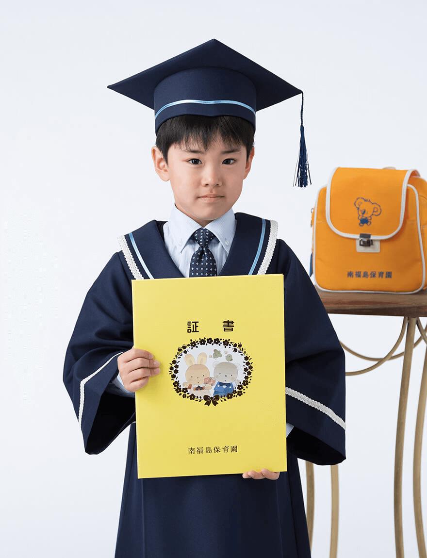 幼稚園卒園写真:幼稚園の制服を着て卒園証書を持っている男の子