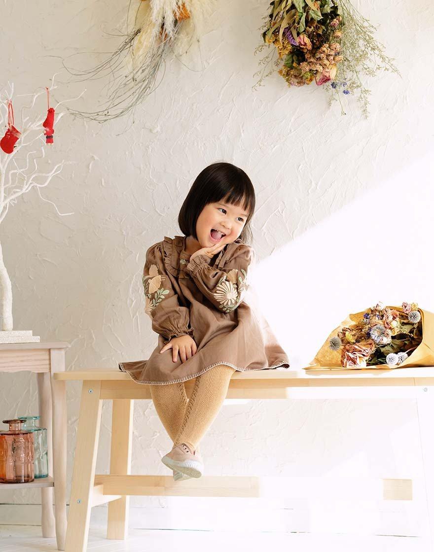 写真:自然光の中、長椅子に座って顎に手を当て、笑顔の女の子
