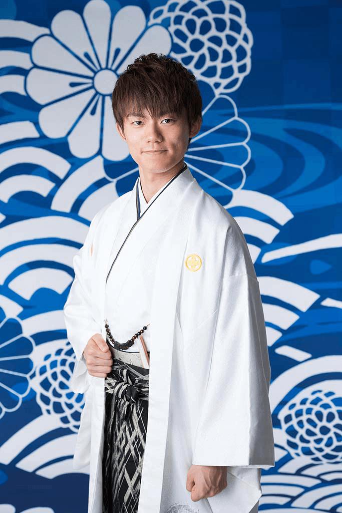 成人式撮影:青い和柄を背景に、羽織袴を着た成人男性の写真
