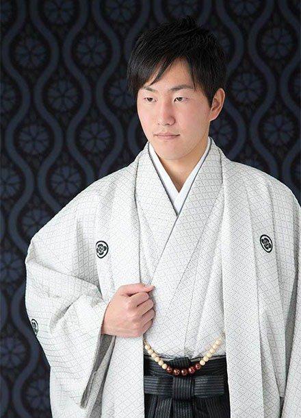 成人式撮影:黒い和柄の背景に、羽織袴を着た成人男性の写真