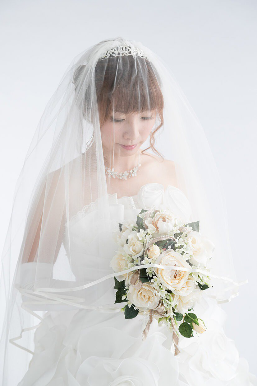 写真:純白のウエディングドレスにブーケを持って幸せそうに微笑んでいる新婦