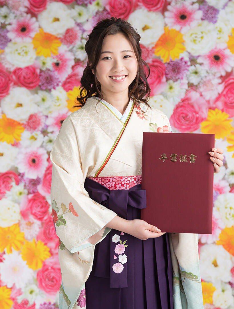 卒業証書を持って卒業写真撮影をする女性